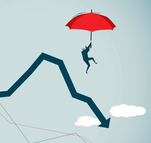 A man using an umbrella to protect against falling stock market prices.