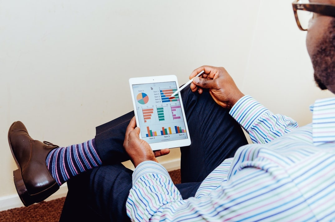 A man checking his stock portfolio on a tablet computer.